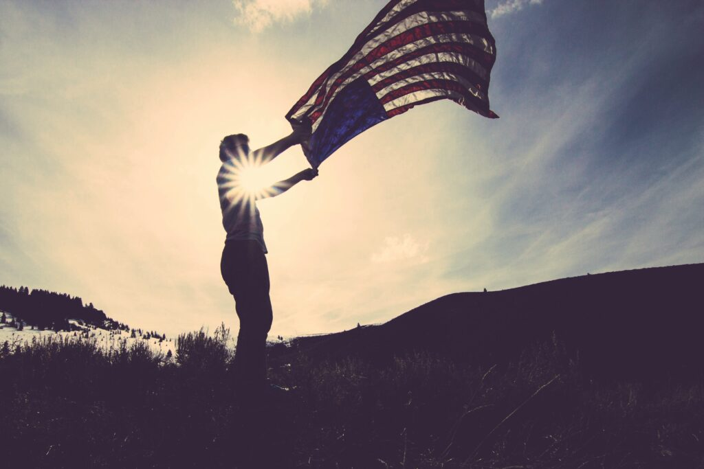 Man with American flag flying in the wind